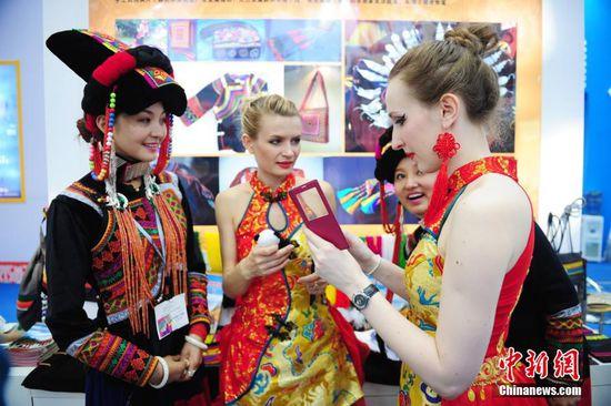 5月14日,第十一届中国(深圳)国际文化产业博览交易会在会展中心开幕,中国少数民族服饰展会上靓丽绽放。图为洋模特与中国彝族服饰姑娘交流。