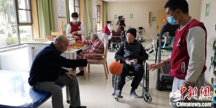 资料图:护工正在和老年人进行康复训练。 贵州省民政厅供图